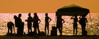 Silhouettes des personnes sur la plage Photo stock