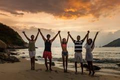 Amis sur la plage au coucher du soleil Photographie stock