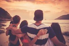 Amis sur la plage au coucher du soleil Photographie stock libre de droits