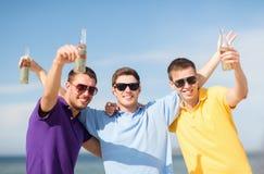 Amis sur la plage avec des bouteilles de boisson Images libres de droits