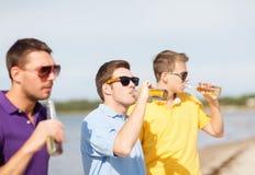 Amis sur la plage avec des bouteilles de boisson Photo libre de droits