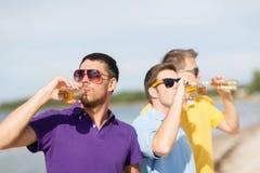 Amis sur la plage avec des bouteilles de boisson Photographie stock libre de droits