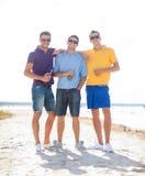 Amis sur la plage avec des bouteilles de boisson Image libre de droits