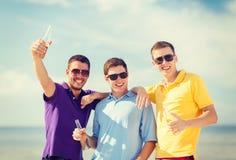 Amis sur la plage avec des bouteilles de boisson Photographie stock