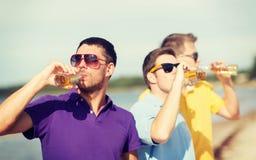 Amis sur la plage avec des bouteilles de boisson Photos stock