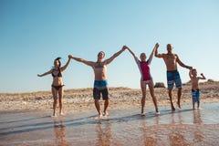 Amis sur la plage Ayez l'amusement au jour d'été ensoleillé Photographie stock libre de droits