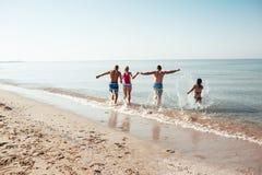 Amis sur la plage Ayez l'amusement au jour d'été ensoleillé Photo stock