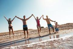 Amis sur la plage Ayez l'amusement au jour d'été ensoleillé Photos stock