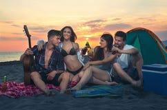 Amis sur la plage dans le coucher du soleil Photos libres de droits