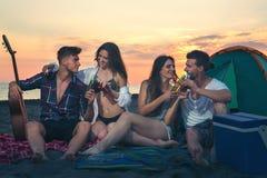 Amis sur la plage dans le coucher du soleil Images libres de droits