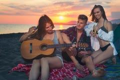Amis sur la plage dans le coucher du soleil Photographie stock libre de droits