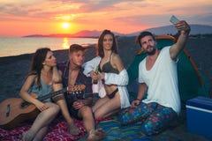 Amis sur la plage dans le coucher du soleil Photo stock
