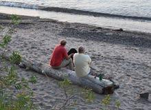 Amis sur la plage du lac Supérieur au coucher du soleil Photos stock