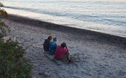 Amis sur la plage du lac Supérieur au coucher du soleil Photo stock