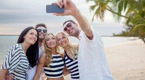 Amis sur la plage prenant le selfie avec le smartphone Photo stock
