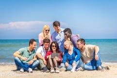 Amis sur la plage regardant le comprimé Image libre de droits