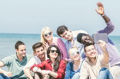 Amis sur la plage regardant le comprimé Images libres de droits
