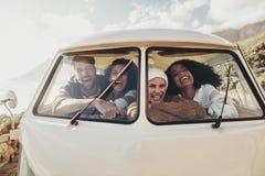 Amis sur la promenade en voiture se reposant à l'intérieur du fourgon Photos stock