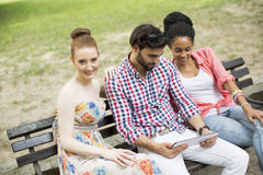 Amis sur le banc avec le comprimé Image stock