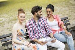 Amis sur le banc avec le comprimé Photos libres de droits