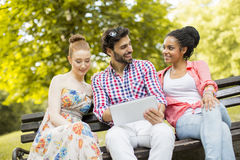 Amis sur le banc avec le comprimé Images libres de droits
