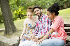 Amis sur le banc avec le comprimé Photographie stock libre de droits