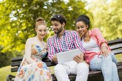 Amis sur le banc avec le comprimé Photo libre de droits