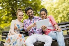 Amis sur le banc avec le comprimé Photo stock