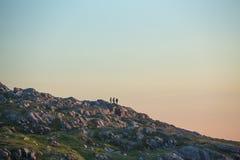 Amis sur le flanc de coteau au coucher du soleil Images libres de droits