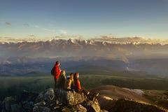 Amis sur le regard supérieur de montagne au coucher du soleil Photo stock