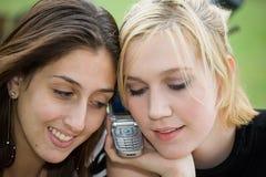 Amis sur le téléphone portable ensemble (belle jeune blonde et Brune Images stock