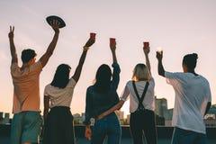 Amis sur le toit au coucher du soleil Photographie stock libre de droits