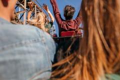 Amis sur le tour de montagnes russes au parc d'attractions Images libres de droits