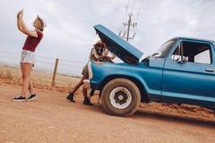 Amis sur le voyage par la route avec la voiture décomposée Photos libres de droits