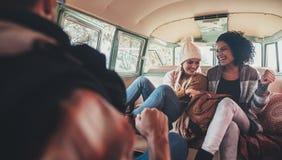 Amis sur le voyage par la route ayant l'amusement à l'intérieur du fourgon Photographie stock libre de droits
