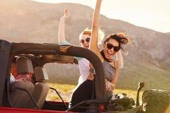 Amis sur le voyage par la route conduisant dans la voiture convertible Photo stock