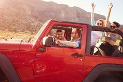 Amis sur le voyage par la route conduisant dans la voiture convertible Photographie stock