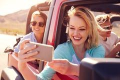 Amis sur le voyage par la route dans la voiture convertible prenant Selfie Images stock