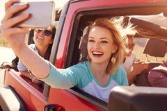 Amis sur le voyage par la route dans la voiture convertible prenant Selfie Photographie stock libre de droits