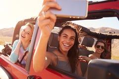 Amis sur le voyage par la route dans la voiture convertible prenant Selfie Photos libres de droits