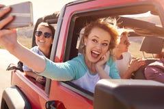 Amis sur le voyage par la route dans la voiture convertible prenant Selfie Image stock