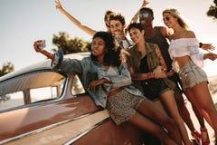 Amis sur le voyage par la route posant pour un selfie Images libres de droits