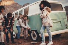 Amis sur le voyage par la route réparant la piqûre de pneu du fourgon images stock
