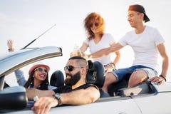 Amis sur le voyage par la route se reposant sur Hood Of Convertible Car Images libres de droits