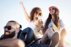 Amis sur le voyage par la route se reposant sur Hood Of Convertible Car Images stock