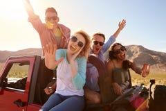 Amis sur le voyage par la route se tenant dans la voiture convertible Photographie stock