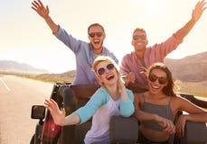 Amis sur le voyage par la route se tenant dans la voiture convertible Image libre de droits