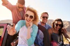 Amis sur le voyage par la route se tenant dans la voiture convertible Images libres de droits
