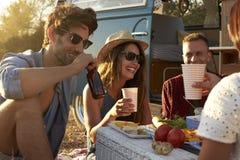 Amis sur un voyage par la route ayant un pique-nique près d'un camping-car Photos libres de droits