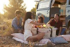 Amis sur un voyage par la route ayant un pique-nique près d'un camping-car Images stock